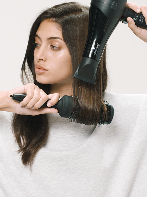 Woman blow drying wavy hair with a round brush.
